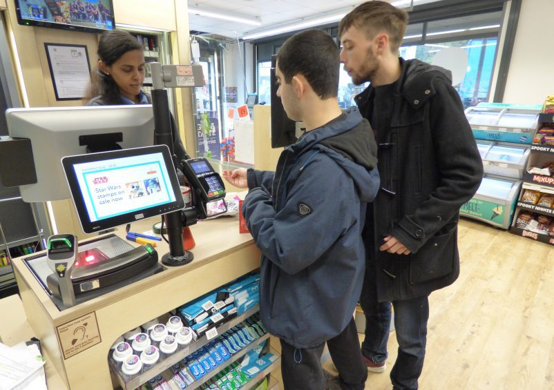 A student paying in a shop